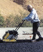 Laborer using a compactor on asphalt