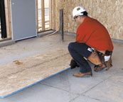 Laborer squatting to grasp plywood