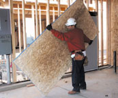 Laborer tilting plywood to one end