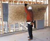 Laborer lifting plywood