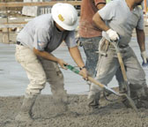 Laborer sliding concrete with a shovel